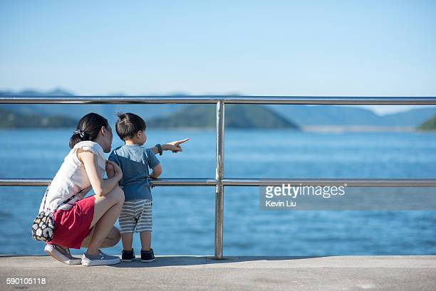 Toddler boy looking at sea with mum