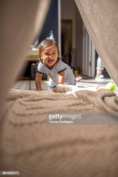 Toddler boy looking through a tent