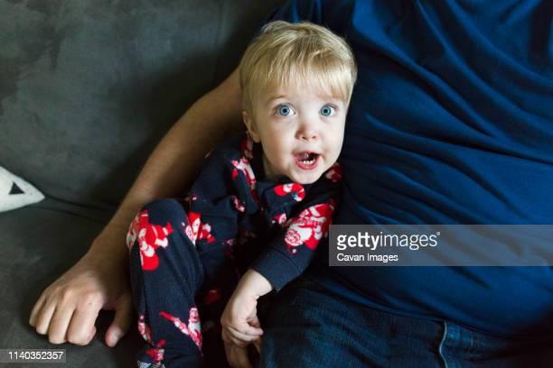 toddler boy looks surprised while sitting next to dad - menino loiro olhos azuis imagens e fotografias de stock