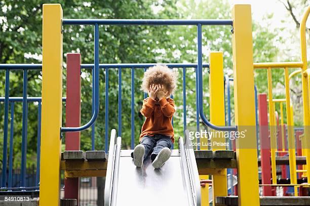 Toddler boy on playground slide