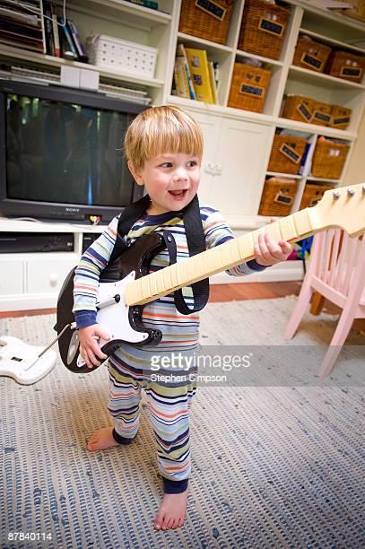 toddler boy playing electric guitar in pajamas