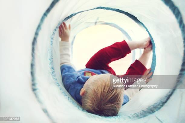 Toddler boy playing in tube