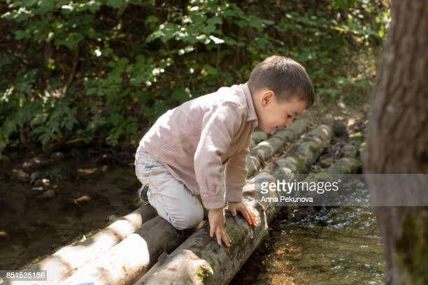 Toddler boy playing on an wooden bridge