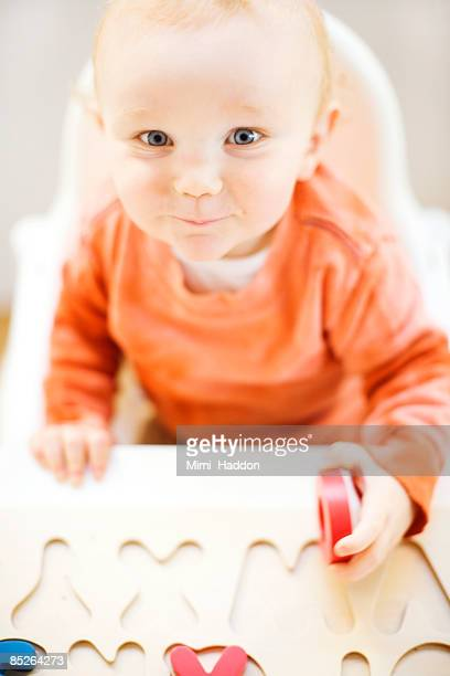 toddler boy playing with alphabet puzzle