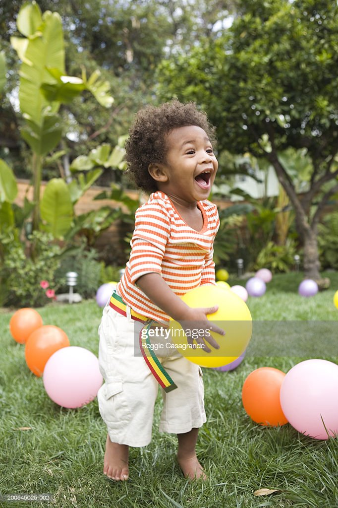 Toddler boy (21-24 months) playing with balloons in yard : Stock Photo
