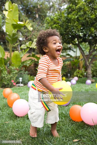 Toddler boy (21-24 months) playing with balloons in yard