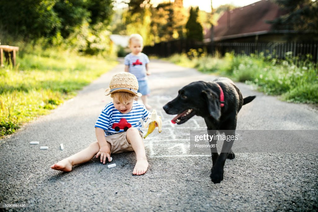Toddler boy playing with chalks on the street : Stock Photo