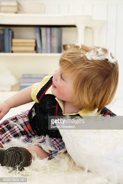 Toddler boy (12-15 months) playing with feather pillow, close-up