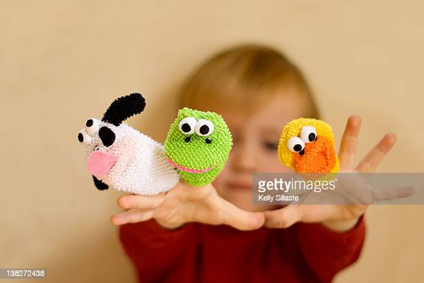 toddler boy playing with finger puppets - puppet stock photos and pictures