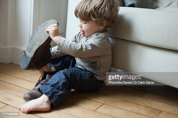 Toddler boy playing with parent's shoes