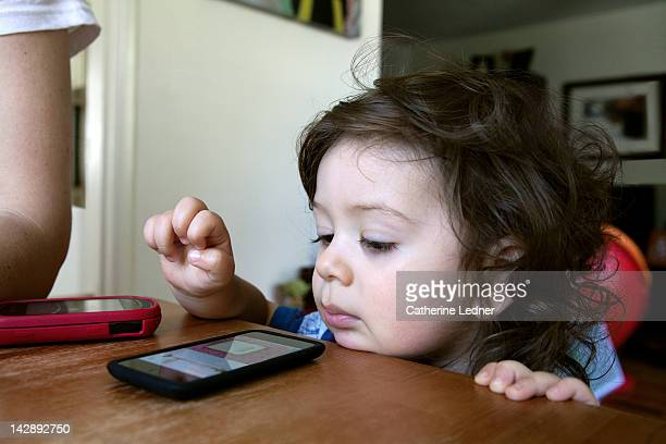Toddler boy playing with smart phone.
