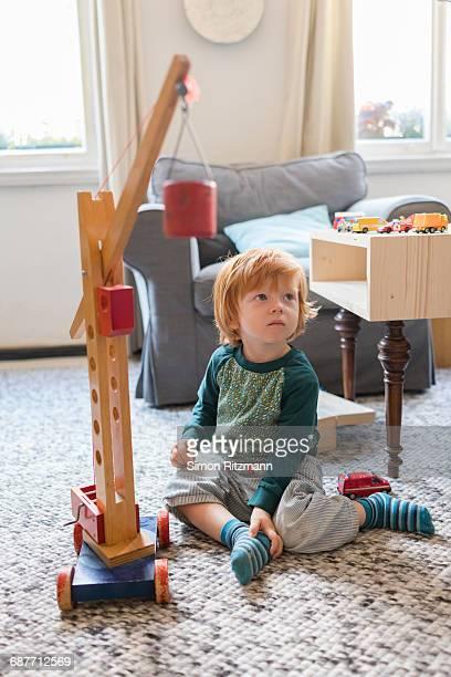 toddler boy playing with wooden crane toy on floor - nur kinder stock-fotos und bilder