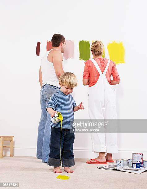 Toddler boy pouring paint on carpet