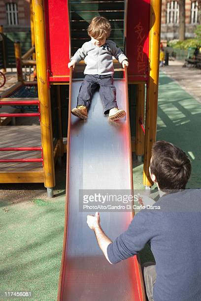 Toddler boy preparing to go down playground slide, father waiting at the bottom