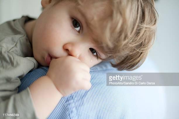 Toddler boy resting head on parent's shoulder, tears on face
