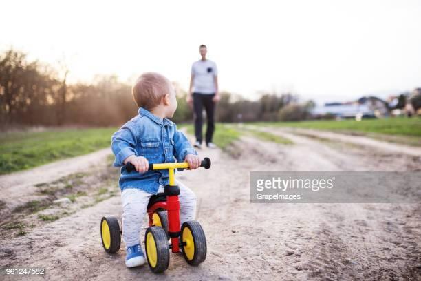 a toddler boy riding tricycle or bicycle outside, looking at his father in the background. - tricycle stock pictures, royalty-free photos & images