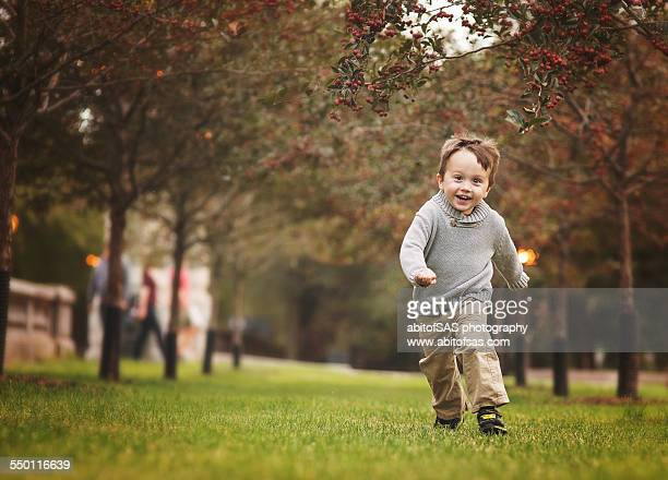 Toddler boy running in park