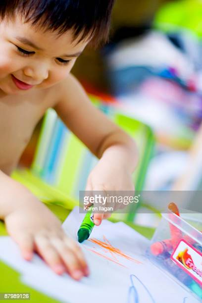 Toddler boy scribbling with crayons