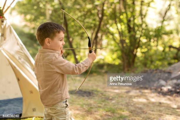 Toddler boy shooting with archery bow