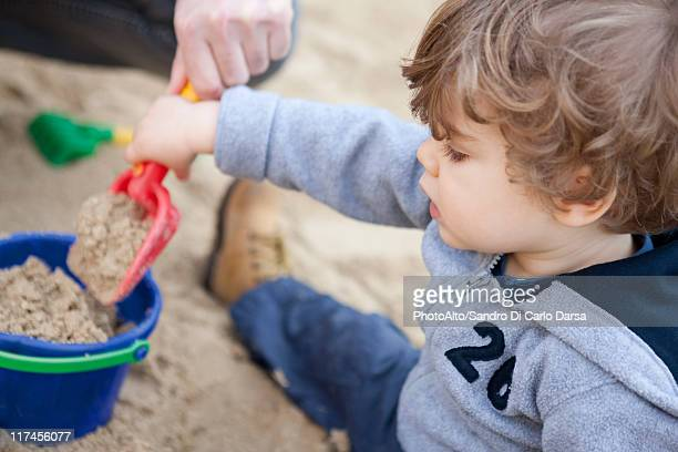 Toddler boy shoveling sand into bucket