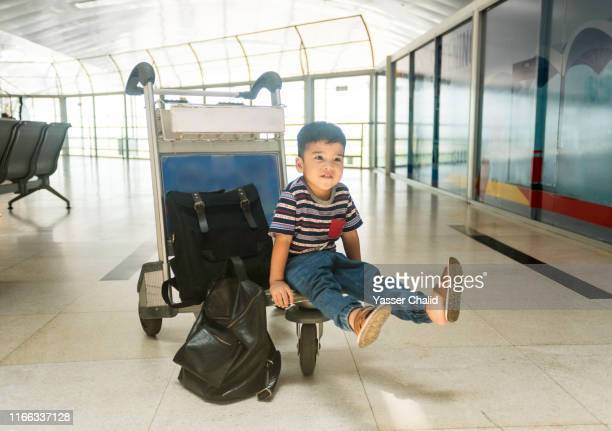 toddler boy sitting at airport - toddler at airport stock pictures, royalty-free photos & images