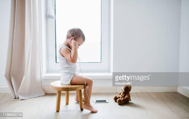 toddler boy sitting on stool at home using smartphone and earphones - junge in unterhose stock-fotos und bilder