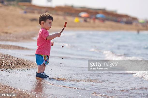 Toddler boy slipping wet sand at sea