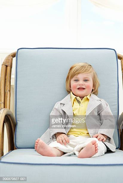 Toddler boy (12-15 months) smiling in arm chair, portrait, close-up