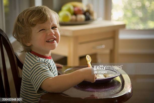 Toddler boy (21-24 months) smiling in high chair, portrait, close-up