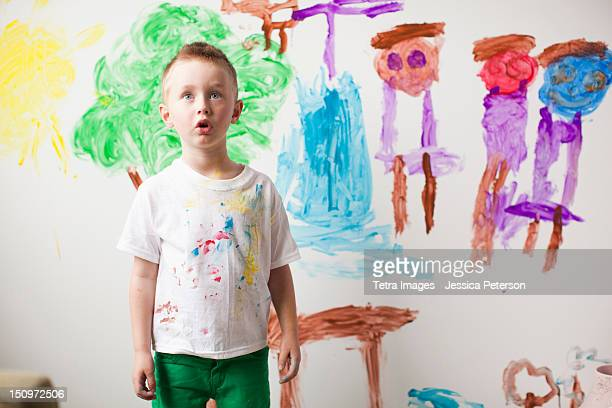 Toddler boy (2-3) standing in front of painted wall