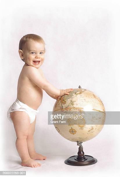 Toddler boy (21-24 months) standing near world globe
