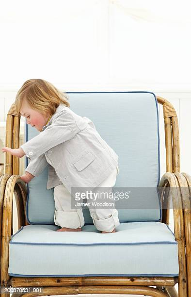 Toddler boy (12-15 months) standing on arm chair, side view