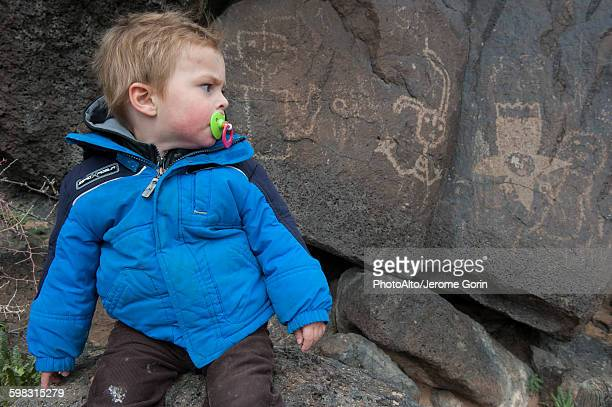 toddler boy studying petroglyph in yellowstone national park, usa - ancient civilization stock photos and pictures