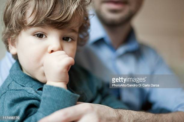 Toddler boy sucking thumb, portrait