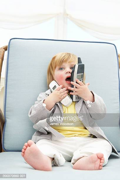 Toddler boy (12-15 months) talking into cell phone and telephone