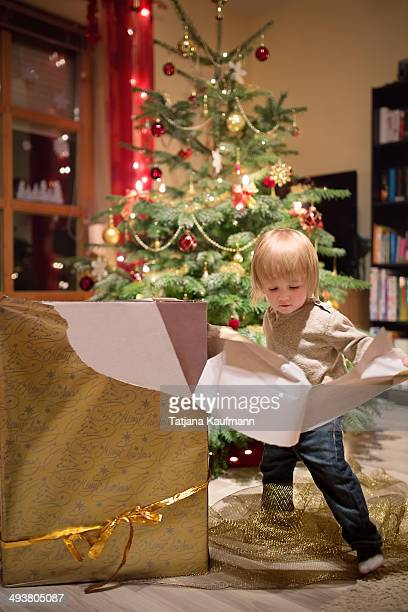 Toddler boy unwrapping Christmas gift box