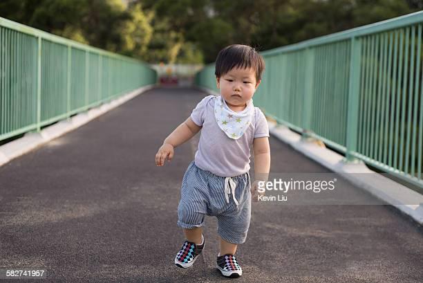 Toddler boy walking on a footbridge