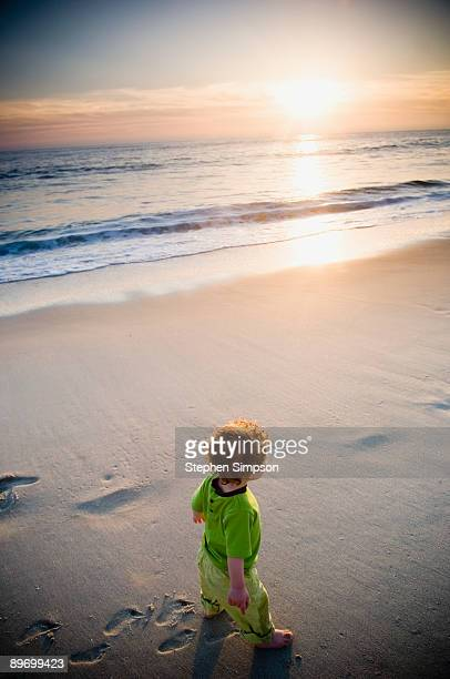 Toddler boy walking on beach