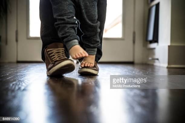 toddler boy (2 yrs) walking on father's feet, closeup - image stock pictures, royalty-free photos & images