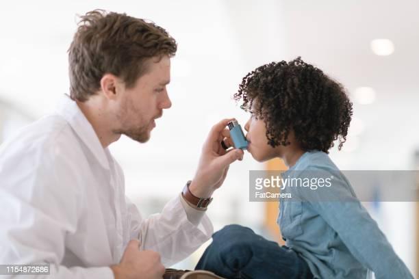 o menino da criança com asma aprende usar o inalador - asmático - fotografias e filmes do acervo