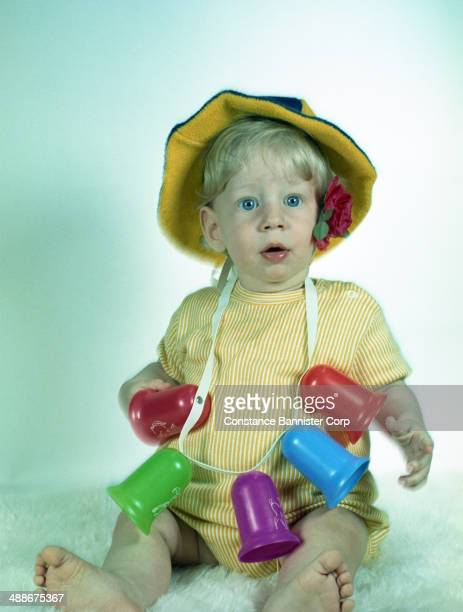 Toddler boy with blond hair wearing a yellow hat and red rose with plastic bells around his neck Syosset New York 1955