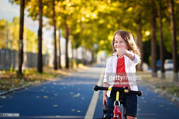 Toddler boy with long hair on a bike