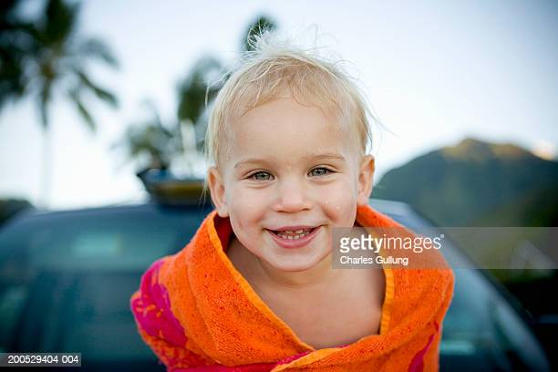 Toddler boy (18-21 months) wrapped in towel, smiling, portrait