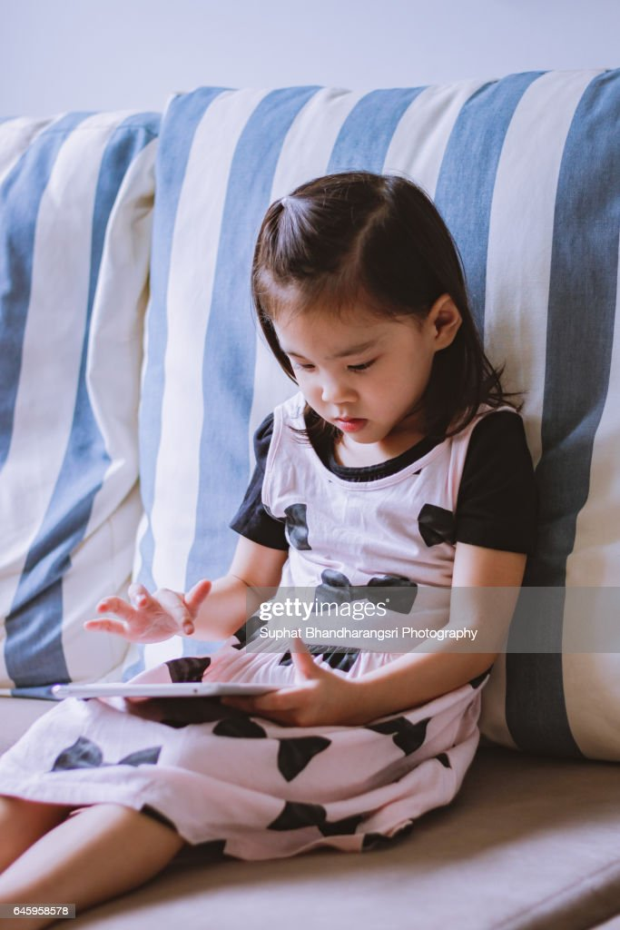 Toddler browsing for her favourite video : Stock Photo