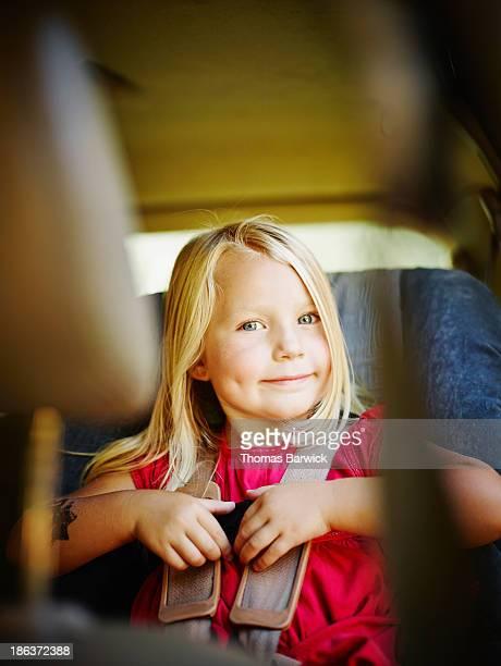 Toddler buckling herself in car seat in car
