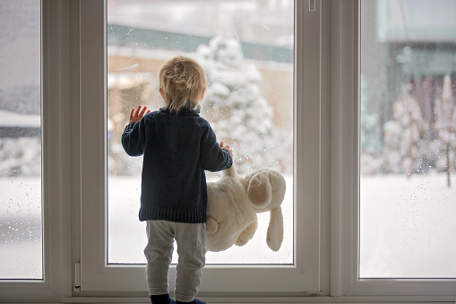 Toddler child standing in front of a big french doors, leaning against it looking outside at a snowy nature 1131383989