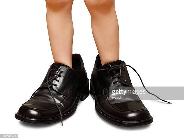toddler childs legs wearing oversized mens dress shoes isolated - big foot stock photos and pictures