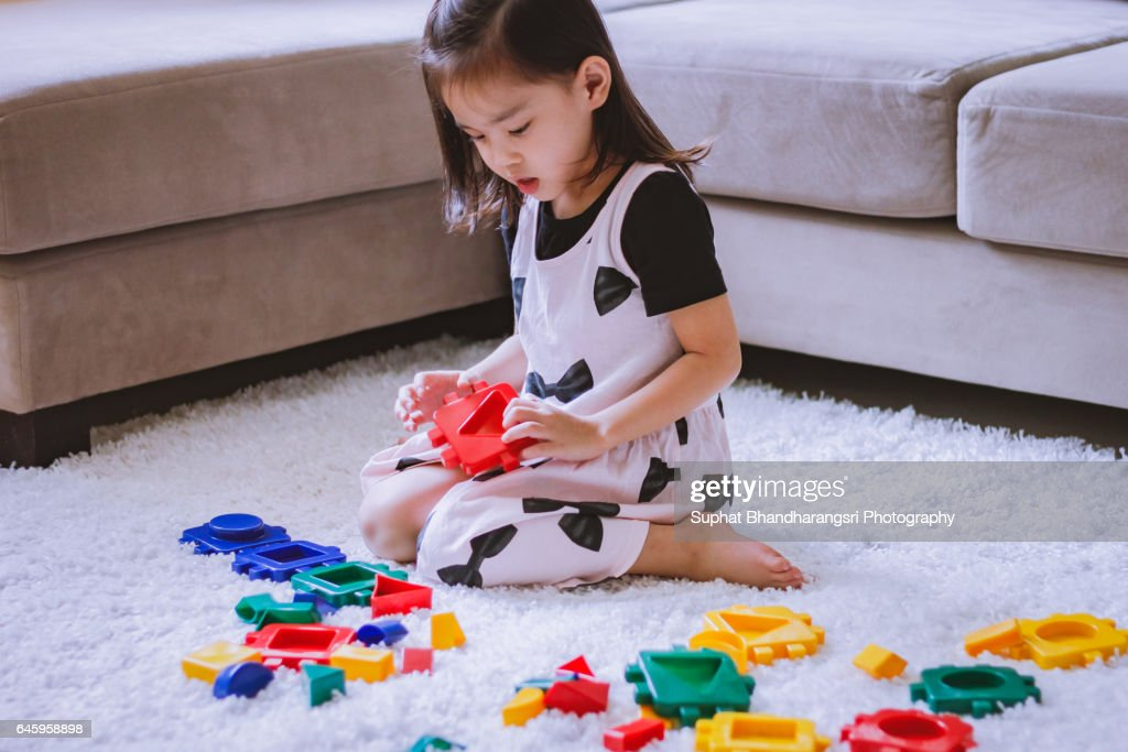 Toddler choosing a toy block : Stock Photo