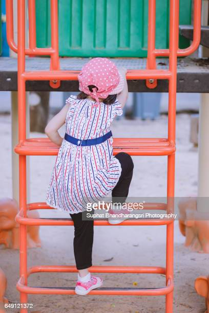 Toddler climbing a ladder of the playhouse