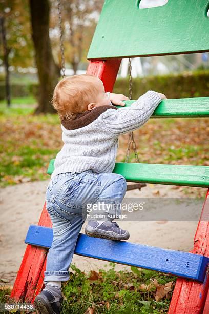 Toddler climbing on jungle gym, Osijek, Croatia